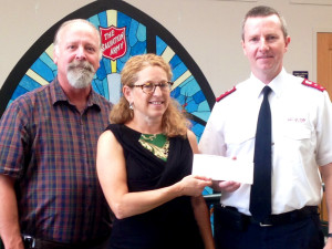 Julie Lapham, ENH Power Community Outreach Coordinator, presents a check to Rick Marshall (L) and Herb Rader (R) of the Salvation Army of Manchester.