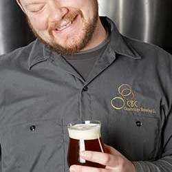 Man smiling down at beer in glass